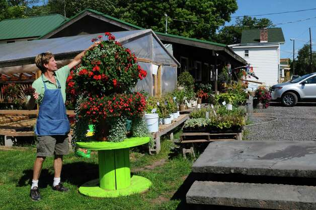 Drew Schuster tends to flowers outside of his restored Catskill Mountain Country Store, damaged by the swollen Batavia Kill in August 2011 as a result of heavy rains from Tropical Storm Irene, on Tuesday Aug. 21, 2012 in Windham, NY. Two cars sank into the formerly shattered parking area where he now stands.  (Philip Kamrass / Times Union) Photo: Philip Kamrass / AL