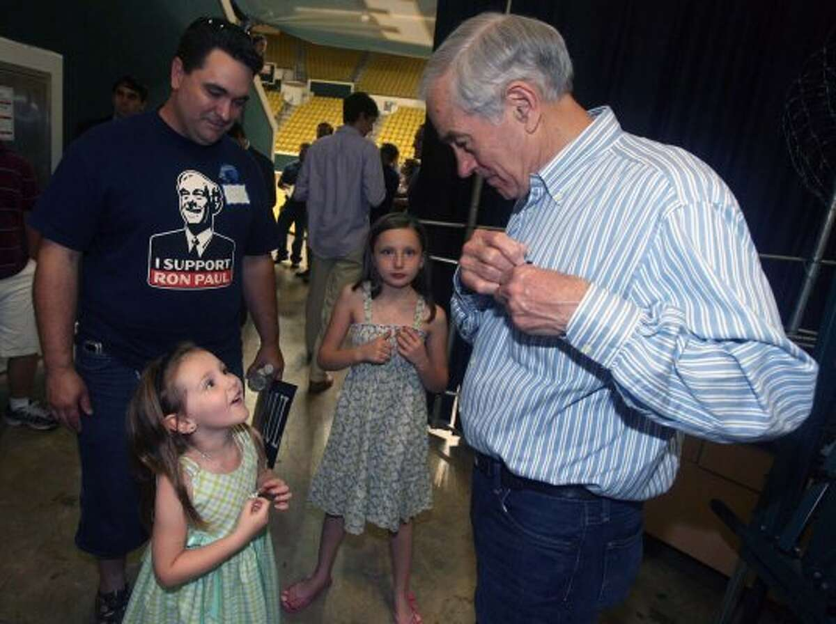 Ron Paul visits with supporters Chris Hand and daughters Arianna Hand, 5, and Skiilyn Hand, 9, after speaking during a Campus Town Hall Meeting Friday night, March 23, 2012 at Southeastern Louisiana University. (Kerry Maloney / The Associated Press)