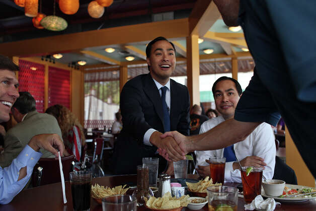 Congressional candidate Joaquin Castro, left, shakes hand with cameraman Dave Roberson as Castro arrives to be interviewed with his brother, Mayor Julian Castro, right, by CBS News National Correspondent Lee Cowan, far left, as they tape a segment for the CBS Evening News at Rosario's in San Antonio on Friday, August 24, 2012. The segment will air the night Castro gives the keynote speech at the Democratic National Convention, Photo: Lisa Krantz, San Antonio Express-News / San Antonio Express-News
