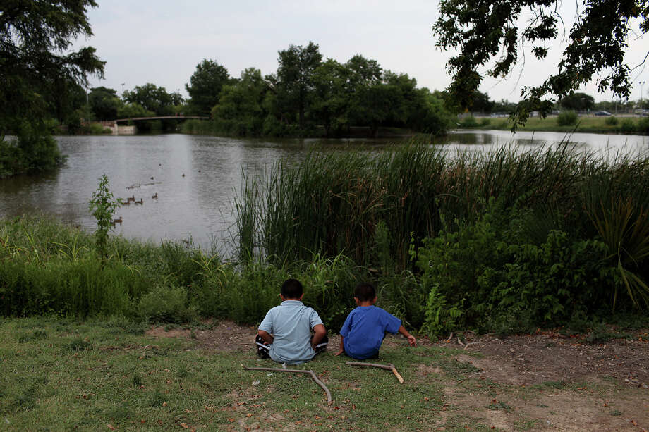 David Marin III, 5, left, and his brother, Dominic Marin, 3, entertain themselves at Elemendorf Lake and Park in San Antonio on Tuesday, August 21, 2012. The boys come to the park almost every day with their parents. Photo: Lisa Krantz, San Antonio Express-News / San Antonio Express-News