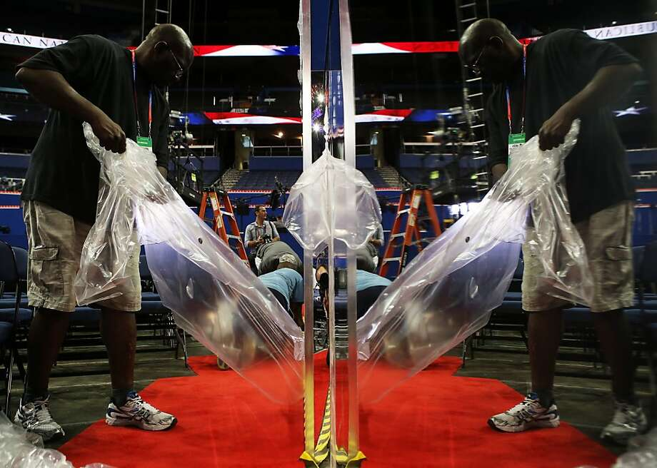 A worker removes the plastic from a mirror on the floor ahead of the Republican National Convention at the Tampa Bay Times Forum on August 26, 2012 in Tampa, Florida. The RNC is scheduled to convene on August 27 and will hold its first session on August 28 as Tropical Storm Isaac threatens disruptions due to its proximity to the Florida peninsula.  (Photo by Chip Somodevilla/Getty Images) Photo: Chip Somodevilla, Getty Images