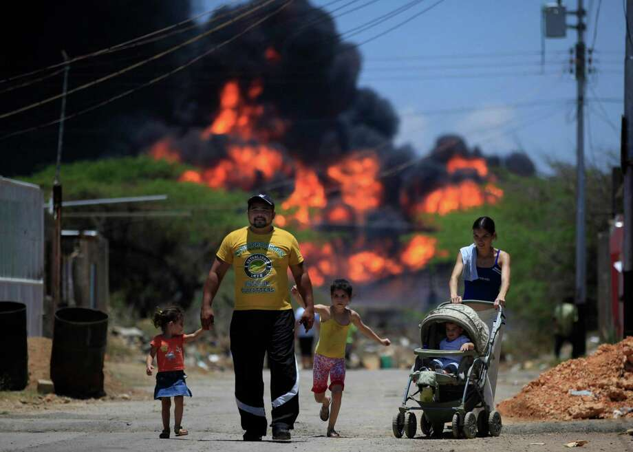 Members of a family walk on a street as flames rise after an explosion in the Amuay refinery near Punto Fijo, Venezuela, Sunday, Aug. 26, 2012. Venezuelans who live next to the country's biggest oil refinery said they smelled a strong odor of sulfur hours before a gas leak ignited in an explosion on Saturday that killed at least 39 people and injured more than 80. (AP Photo/Ariana Cubillos) Photo: Ariana Cubillos / AP