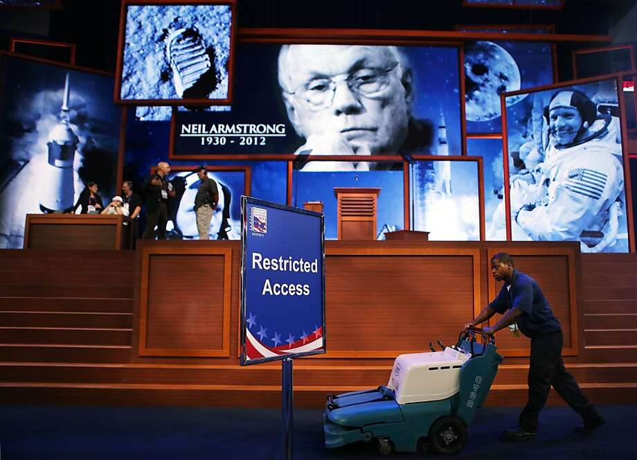 A man pushes a vacuum in front of a tribute displayed on stage for recently deceased NASA astronaut Neil Armstrong ahead of the Republican National Convention at the Tampa Bay Times Forum on August 26, 2012 in Tampa, Florida. The RNC is scheduled to convene on August 27 and will hold its first session on August 28 as Tropical Storm Isaac threatens disruptions due to its proximity to the Florida peninsula.  (Photo by Chip Somodevilla/Getty Images) Photo: Chip Somodevilla, Getty Images