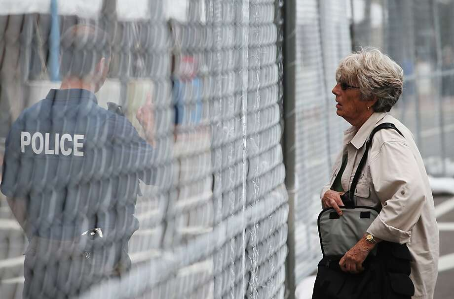 A woman stands on one side of a security fence as a police officer directs her ahead of the Republican National Convention outside the Tampa Bay Times Forum on August 26, 2012 in Tampa, Florida. The RNC is scheduled to convene on August 27 and will hold its first session on August 28 as Tropical Storm Isaac threatens disruptions due to its proximity to the Florida peninsula.  (Photo by Scott Olson/Getty Images) Photo: Scott Olson, Getty Images