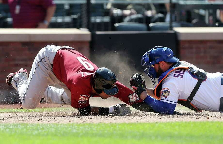 Marwin Gonzalez tried to sneak under the tag of Mets catcher Kelly Shoppach in the ninth but was called out and earned an ejection for protesting the decision. Photo: Jim McIsaac / 2012 Getty Images