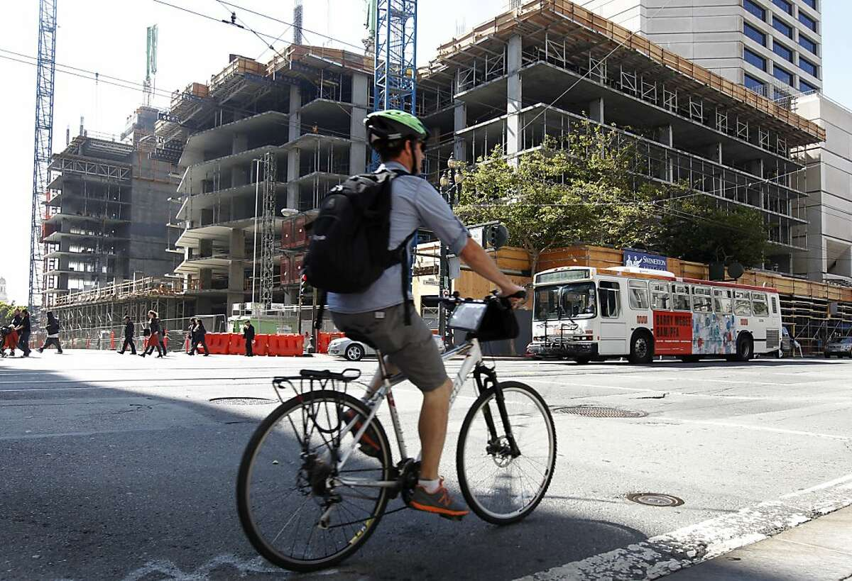 A bicyclist pedals past a large residential complex under construction at 10th and Market streets in San Francisco, Calif. on Friday, Aug. 24, 2012.