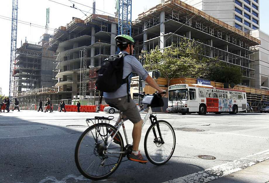 A bicyclist rides past a large residential complex under construction at 10th and Market streets, near the new Twitter headquarters. Photo: Paul Chinn, The Chronicle
