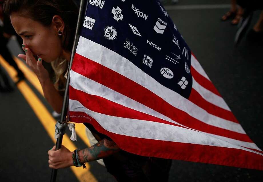 A woman holds a flag during a demonstration through downtown on August 26, 2012 in St. Petersburg, Florida. The demonstration was being held on the eve of the start of the Republican's nominating convention which will hold its first session on August 28. The convention was scheduled to start on August 27 but was pushed back one day as Tropical Storm Isaac threatens to hit the Tampa area.  (Photo by Tom Pennington/Getty Images) Photo: Tom Pennington, Getty Images