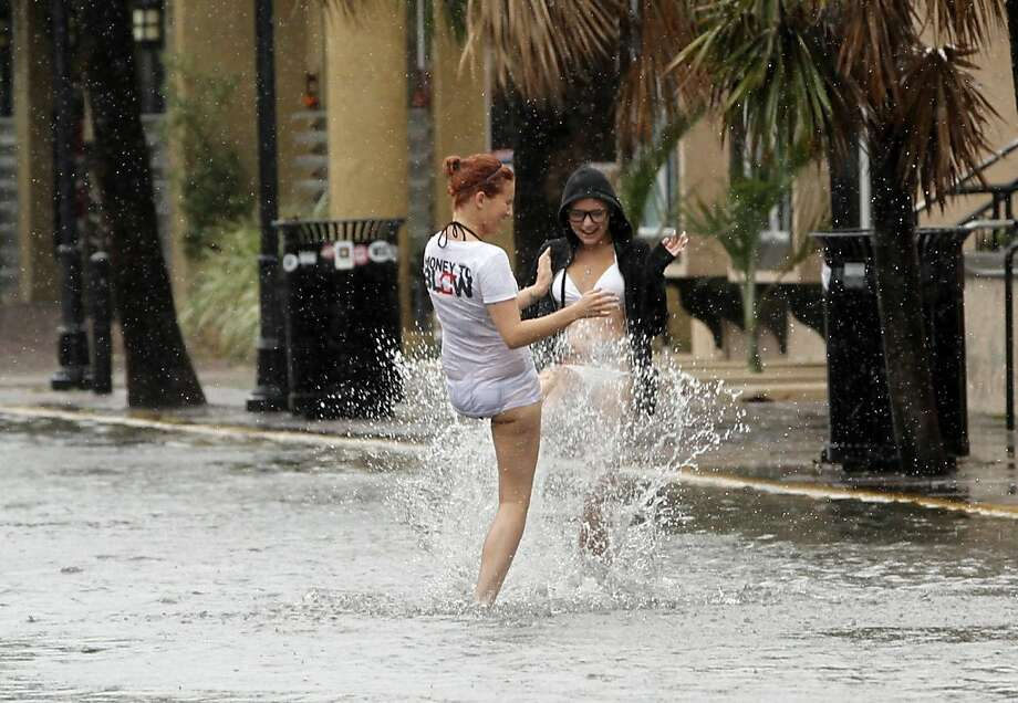 Heather Boss, right, and Brittney Lambert, both of Oklahoma, have fun in a flooded street due to heavy rains in Key West, Fla., Sunday, Aug. 26, 2012 as heavy storm winds and rain hit the northern coast. Rain bands from Tropical Storm Isaac are expected to continue streaming across Marion County Monday as the ninth named storm of the 2012 hurricane season continues toward the northern Gulf of Mexico. National Weather Service officials in Jacksonville on Sunday said Marion County began getting rain bands from Isaac around 2 p.m. and that the rain would continue through Tuesday. (AP Photo/Alan Diaz) Photo: Alan Diaz, Associated Press