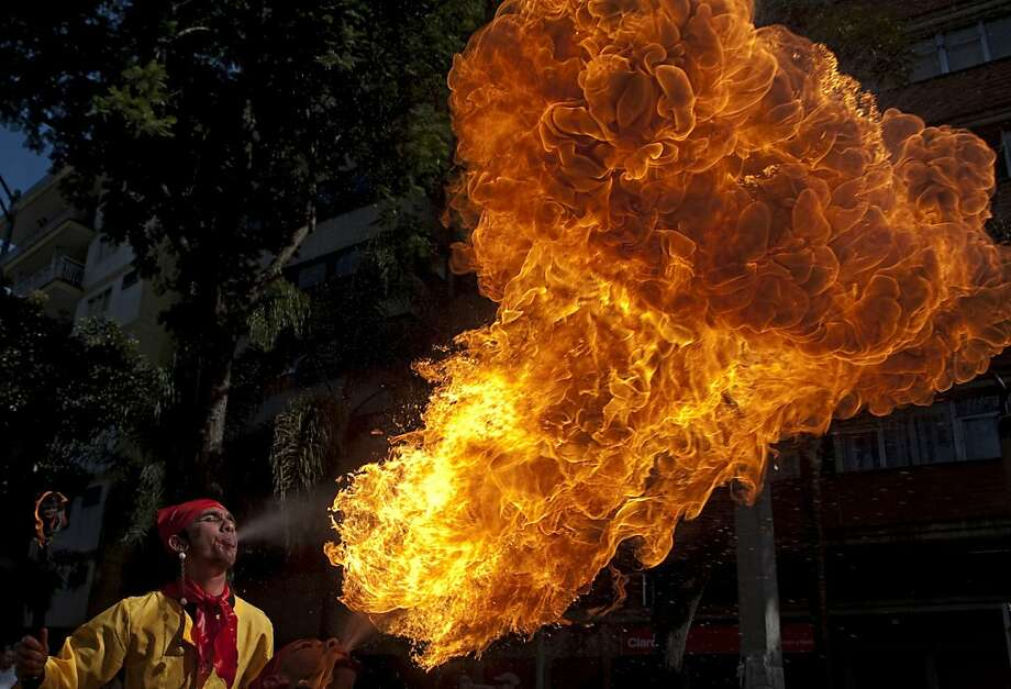 An artist throws fire from his mouth during the Stage Arts Festival in the streets of Medellin, Antioquia department, Colombia on August 26, 2012. AFP PHOTO/Raul ARBOLEDARAUL ARBOLEDA/AFP/GettyImages Photo: Raul Arboleda, AFP/Getty Images