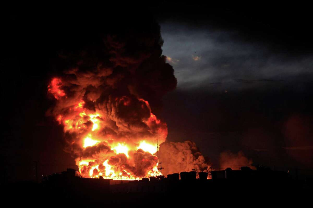A large fire rises over the Amuay refinery near Punto Fijo, Venezuela, Saturday, Aug. 25, 2012. A huge explosion rocked Venezuela's biggest oil refinery, killing at least 24 people and injuring dozens, an official said. (AP Photo/Ariana Cubillos)