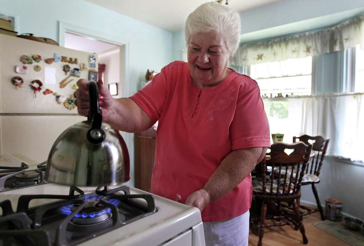 """In this photo taken July 26, 2012, Marge Youngs adjusts the flame on her stove at her home in Toledo, Ohio. When given a choice on how to fix Social Security's serious long-term financial problems, 53 percent of adults said they would rather raise taxes than cut benefits for future generations, according to an Associated Press-GfK poll. """"Right now, it seems like we're taxed so much, but if that would be the only way to go, I guess I'd have to be for it to preserve it,"""" said Youngs, a 77-year-old widow. """"It's extremely important to me. It's most of my income."""" (AP Photo/Carlos Osorio)"""