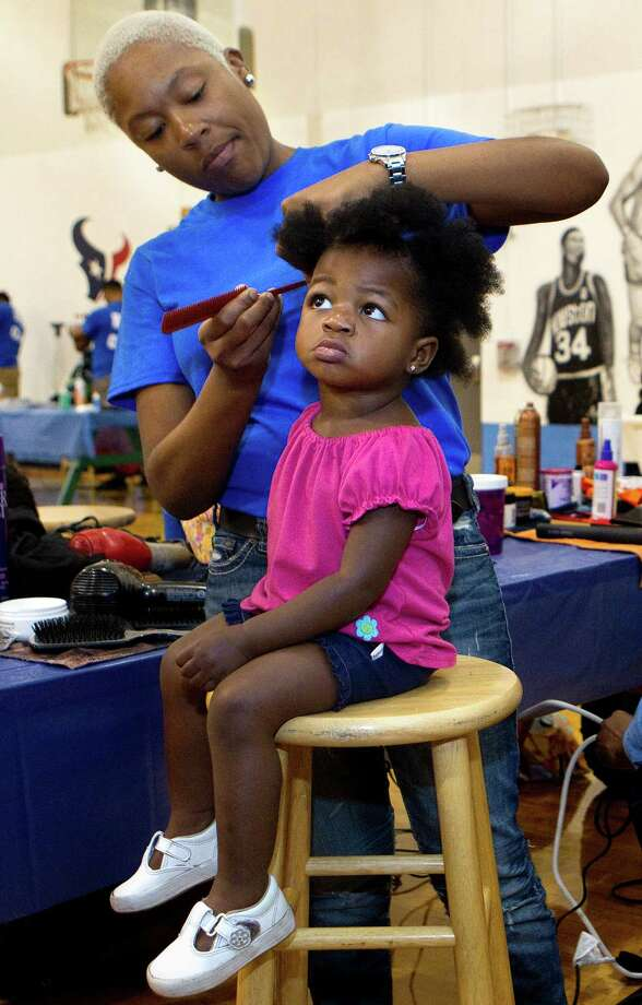 """Tia Carmbs cuts 1-year-old Brook Madison's hair Sunday at the fourth annual """"Look Good, Feel Good"""" event at Fort Bend Boys and Girls Club. The event provided students free haircuts, hair supplies backpacks and school supplies. Photo: Cody Duty / © 2011 Houston Chronicle"""