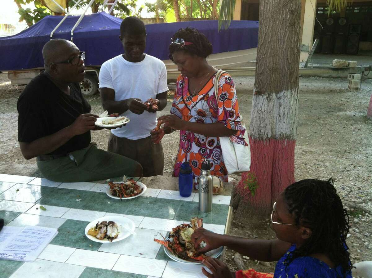 Roberto Bonheur, left, eats a meal with his wife, Rose Bonheur, right, during a recent humanitarian mission to Haiti. The man in the center is unidentified. Miriam Cajuste sits at the table. (Miriam Cajuste)