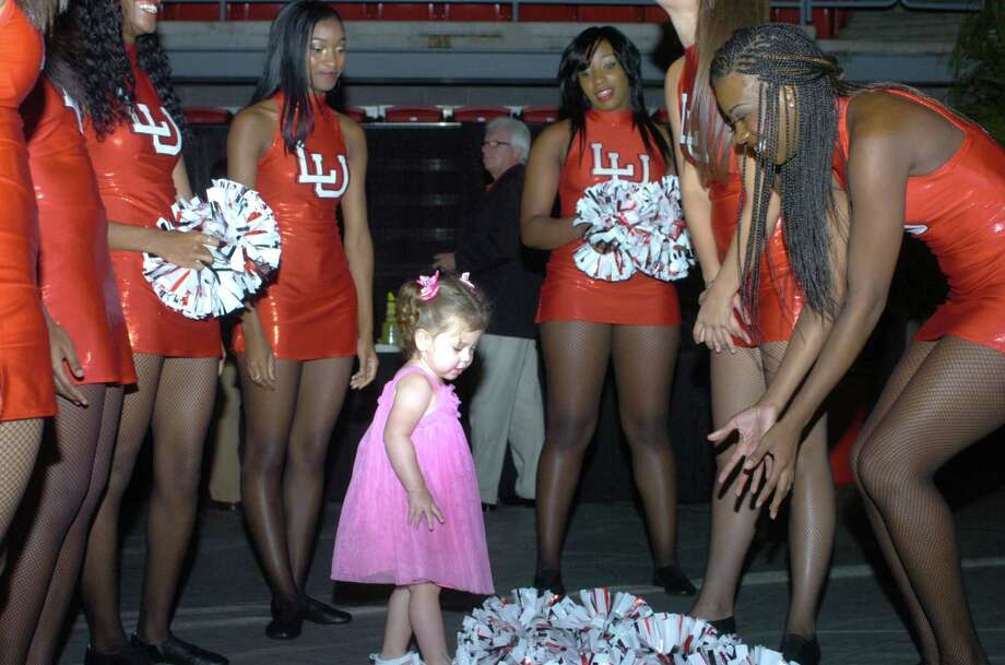 Brayla Hildreath, 19-month-old daughter of Lamar University football player Kye Hildreth, instructs some dance team members on proper pom-pom technique at the Cardinals kickoff celebration Sunday night. Photo: Sarah Moore