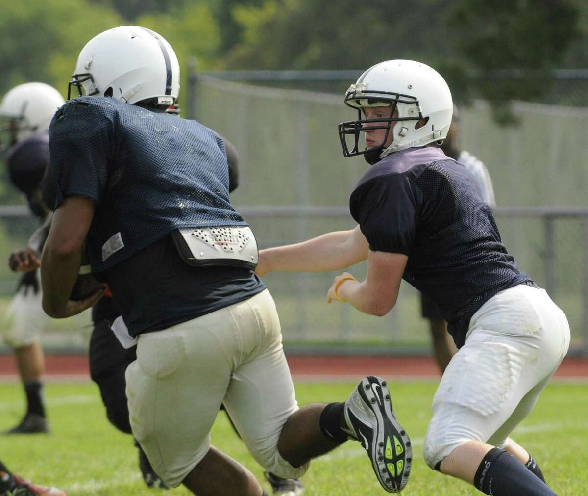 Rensselaer High School football quarterback Steve Harwood hands the ball off Seth Butle to during a scrimmage with Voorheesville in Albany, NY Saturday Aug. 25, 2012. (Michael P. Farrell/Times Union)