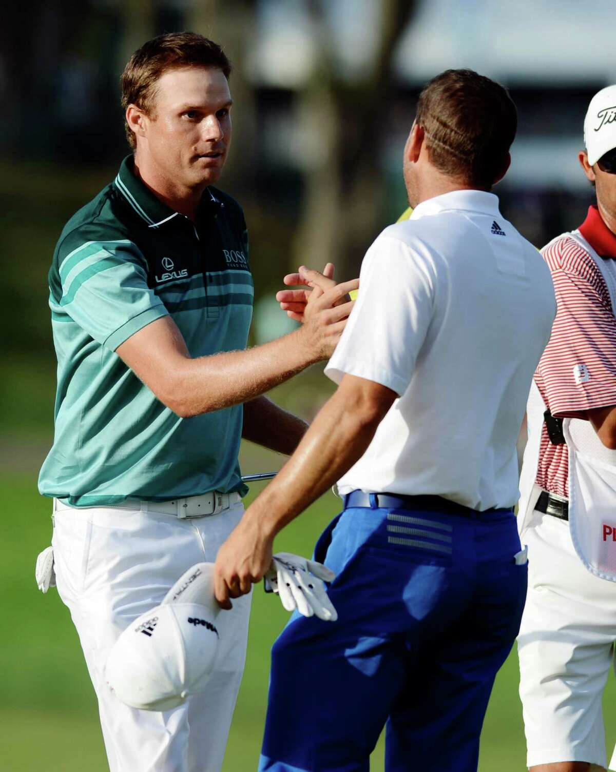 Nick Watney, left, shakes hands with his playing partner, Sergio Garcia, of Spain, after sinking a birdie putt on the 18th hole of the fourth round to win The Barclays golf tournament at Bethpage State Park in Farmingdale, N.Y., Sunday, Aug. 26, 2012. (AP Photo/Henny Ray Abrams)