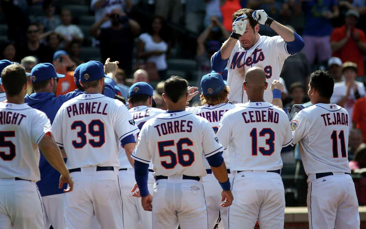 New York Mets' Ike Davis jumps into waiting teammates after hitting the game-winning home run in the ninth inning of a baseball game against the Houston Astros at Citi Field in New York, Sunday, Aug. 26, 2012. (AP Photo/Craig Ruttle)