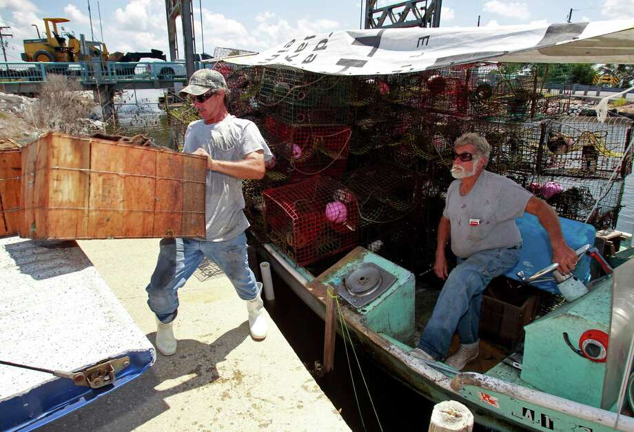Crabbers Tommy and Aln Squires unload their boat in Bayou La Loutre in St. Bernard Parish, La., on Sunday as they prepare for tropical storm Isaac. Photo: JOHN MCCUSKER / THE TIMES-PICAYUNE