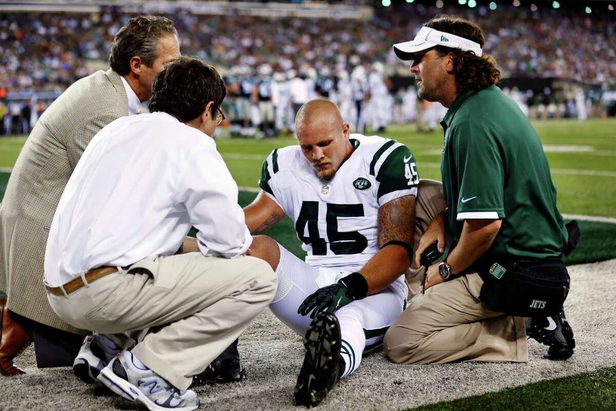 Trainers help New York Jets tight end Josh Baker (45) after he was injured during the first half of a preseason NFL football game against the Carolina Panthers, Sunday, Aug. 26, 2012, in East Rutherford, N.J. (AP Photo/Julio Cortez)
