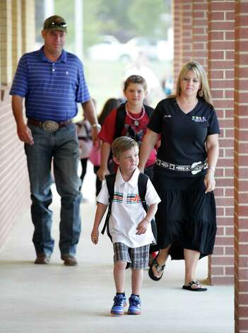Cade Sandstrom, 5, leads his family,  father John Sandstrom, left to right, brother Chase Sandstrom 9, and mother Jennifer, on his way to his first day of Kinder at Los Reyes Elementary School, the newest school in the Northside  ISD.  Monday, Aug. 27, 2012. Photo: Bob Owen, San Antonio Express-News / © 2012 San Antonio Express-News