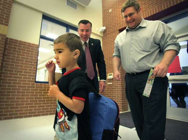 Jayson Stier, 5, arrives at Los Reyes Elementary School, the newest school in the Northside ISD, with his father James Stier, right, as they were greeted by the new Superintendent of Northside ISD, Brian Woods, center.  Monday, Aug. 27, 2012. Photo: Bob Owen, San Antonio Express-News / © 2012 San Antonio Express-News