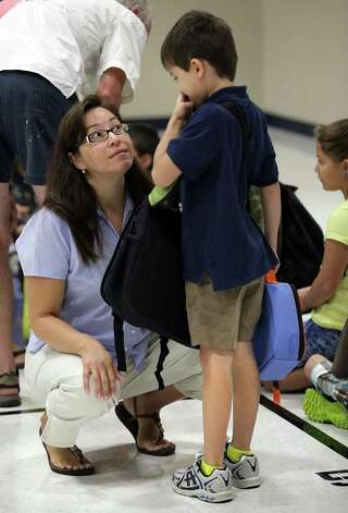 Becky Scheibelhut, left, listens to her son Jake Scheibelhut, 7, as he prepares to go to first day of second grade at Los Reyes Elementary School, the newest school in the Northside  ISD.  Monday, Aug. 27, 2012. Photo: Bob Owen, San Antonio Express-News / © 2012 San Antonio Express-News