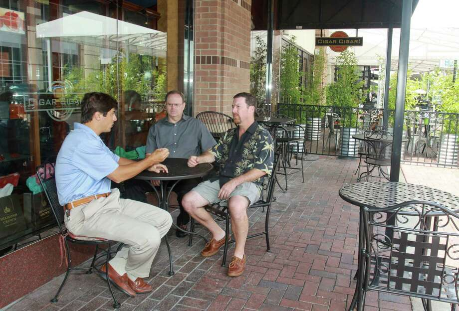"(For the Chronicle/Gary Fountain, August 24, 2012)  Matias Adrogue, a trial lawyer for Cigar Cigar, from left, Cigar Cigar general manager Tom Parks, and owner Rich Tisch, on the patio at Cigar Cigar in Sugar Land Town Square. They are not able to smoke a cigar or pipe on their patio due to a Sugar Land Town Square ban. ""There is no outdoor smoking ban in the city of Sugar Land,"" said Adrogue. Photo: Gary Fountain, For The Chronicle / Copyright 2012 Gary Fountain."
