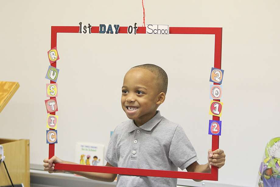 Jordan Henry poses for a picture with a frame made by his new pre-kindergarten teacher Vera Rogers on the first day of school at Rustic Oak Elementary in Pearland. Photo: Nick De La Torre, Houston Chronicle