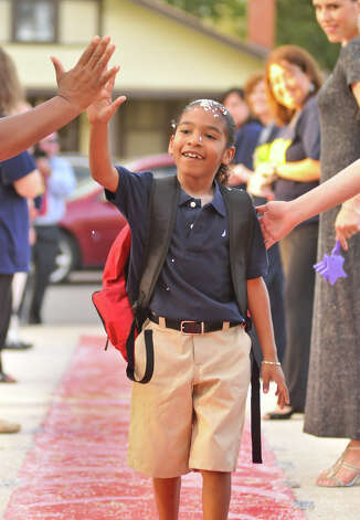 Confetti-covered Franklin Elementary School 3rd grader Demariae  Agosto high-fives teachers as she arrives for the first day of school Monday morning. Teachers put together a red-carpet welcoming for all the students. Photo: Robin Jerstad, Robin Jerstad/For The Express-Ne / Robert Jerstad   !    !RPO-=