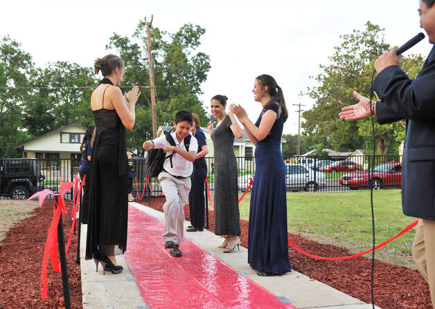 "Franklin Elementary School 4th grader Joseph Mayorga dances up a  ""red carpet"" between teachers Melissa Day, Denise Ramon, and veronica Goldbach. Principal Eduardo Davila (right) is waiting to interview him over a public address system as the new school year got underway Monday morning. Photo: Robin Jerstad/For The Express-News / ROBIN JERSTAD     210 254 6552"