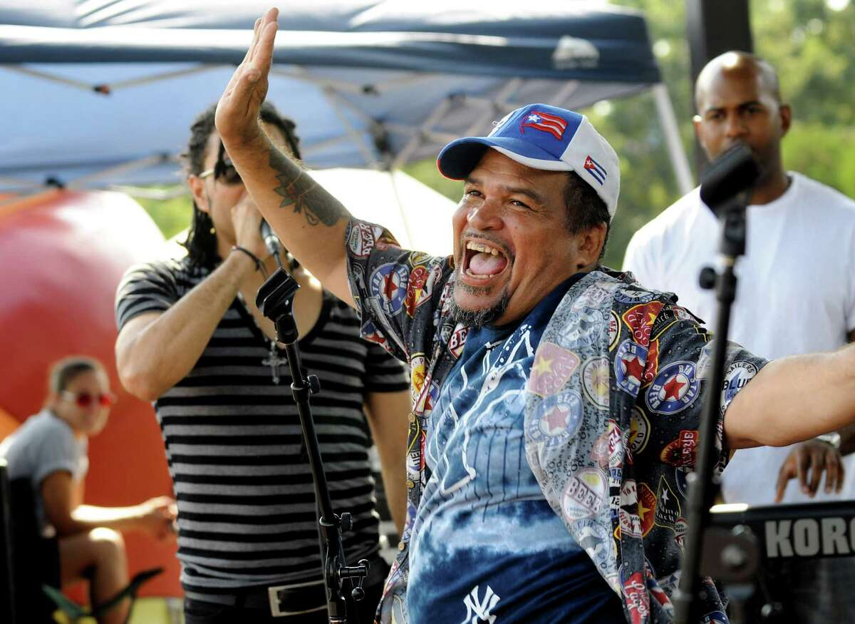 Puerto Rican native Dixon Rodrigues of Troy, center, dances on stage with band Mala Fe during the Albany Latin Fest on Saturday, Aug. 25, 2012, at Washington Park in Albany, N.Y. (Cindy Schultz / Times Union)
