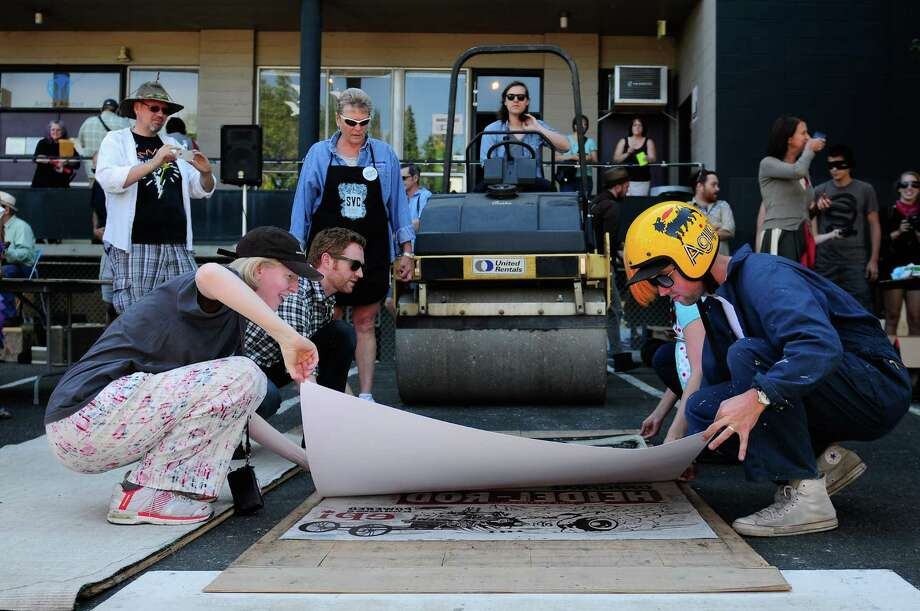 Molly Seibert and Evan Christie pull a protective sheet off of a print during the 11th Annual Letterpress Wayzgoose & Steamroller Smackdown at the School of Visual Concepts in Seattle on Saturday, August 25, 2012. The event, which ended in a silent auction for the one-of-a-kind prints, benefited the school  and  let attendees try out letterpress machines themselves. Photo: LINDSEY WASSON / SEATTLEPI.COM