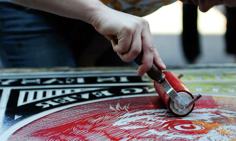 Myrna Knode helps ink a large block by KeegenMeegan & Co.. Photo: LINDSEY WASSON / SEATTLEPI.COM