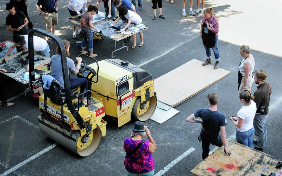 Nita Chambers, top right, secures a wooden board as Christopher Harrell drives over prints with a 2-ton steamroller. Photo: LINDSEY WASSON / SEATTLEPI.COM