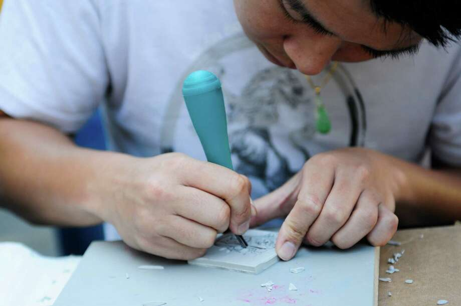 Bryant Truong  works on a safety-cut design at the Blick Art booth. Photo: LINDSEY WASSON / SEATTLEPI.COM