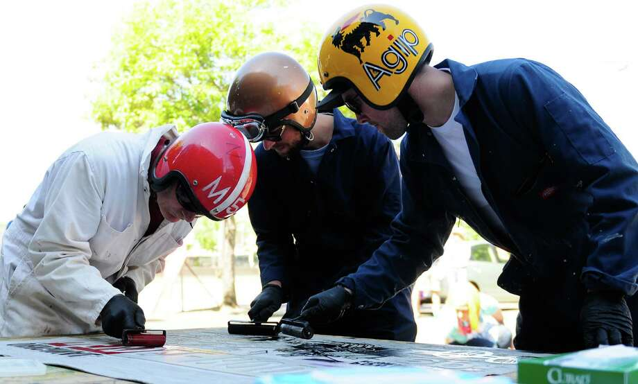 Scott Hill, Jeff Roberge and Evan Christie of Evolution Press work on inking a press to put through the steamroller. Photo: LINDSEY WASSON / SEATTLEPI.COM