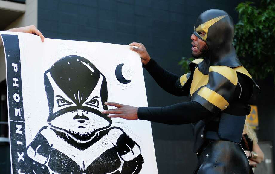 """Phoenix Jones points to his cheeks, saying, """"I think my cheeks are a little fatter in this,"""" during the 11th Annual Letterpress Wayzgoose & Steamroller Smackdown at the School of Visual Concepts. Photo: LINDSEY WASSON / SEATTLEPI.COM"""