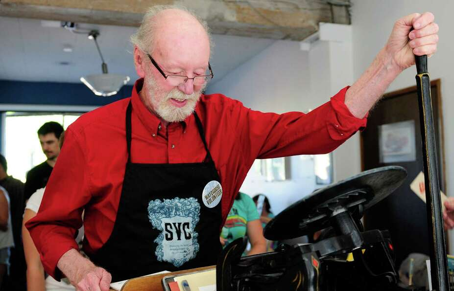 Printmaker Carl Montford makes a print using an 80 year-old Chandler & Price letterpress during the
