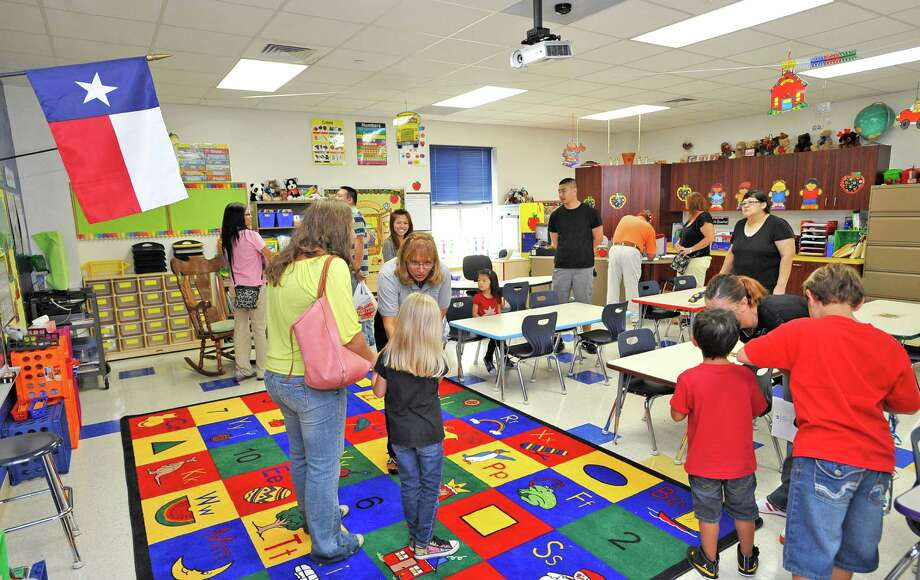 Kindergarden teacher Debra Singleton, center, greets some of her new students. Sallie Curtis Elementary School had its grand opening and official dedication Friday August 24, 2012.  BISD officials, school board trustees, students, teachers and staff were all on hand to help cut the ribbon and then tour the last of the new schools to be built with bond money.   Dave Ryan/The Enterprise