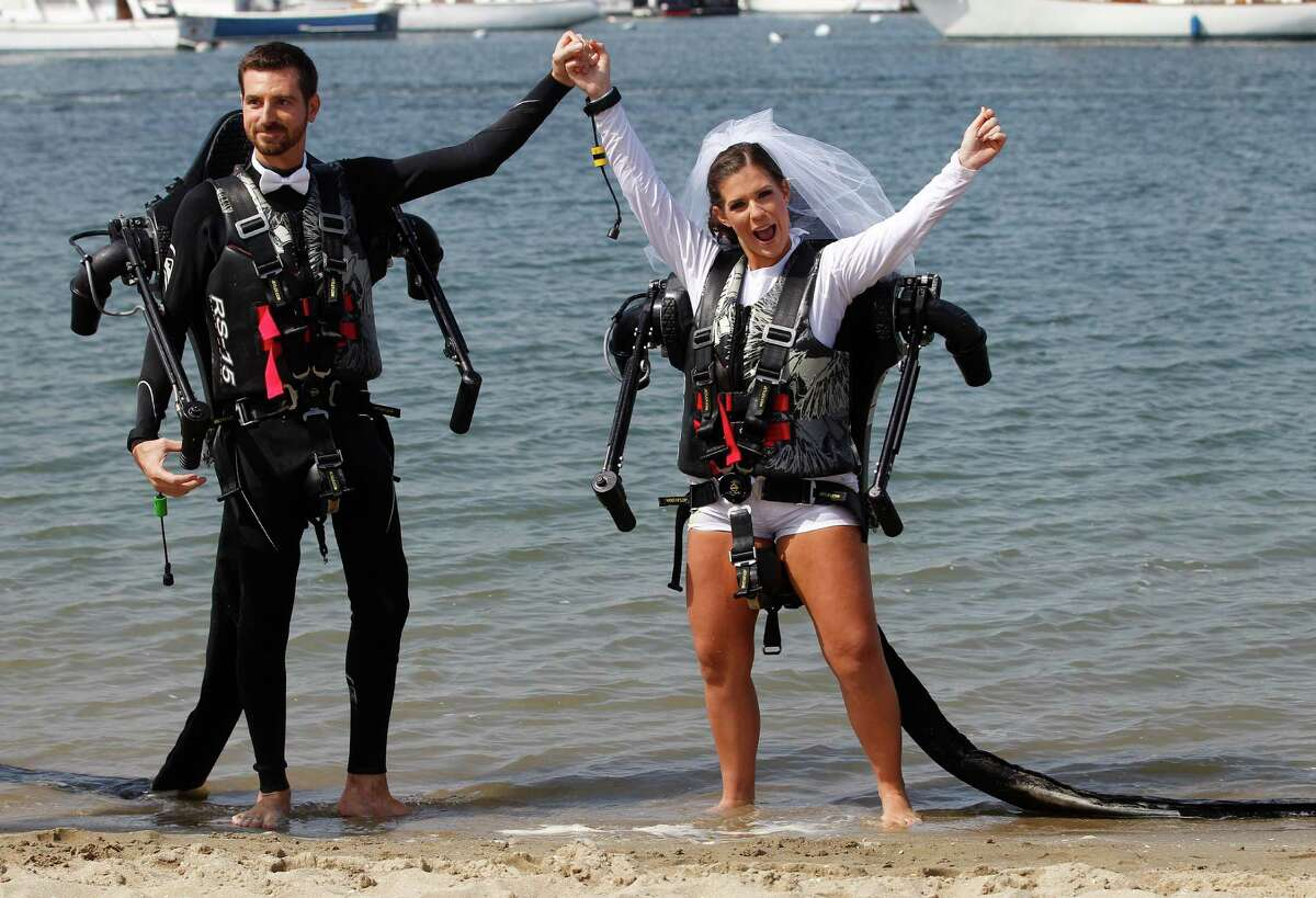 Grant Engler and his new wife, Amanda Engler, celebrate at their wedding ceremony which they arrived for in jet pack suits Thursday, Aug. 23, 2012 in Newport Beach. The 25-year-old former wedding planner from Grand Rapids, Mich., says she wanted a unique ceremony. So the couple donned the (Canadian) $90,000 (C72,000) contraptions on their backs, along with a wetsuit for the groom and white board shorts and a rash-guard shirt for the bride. The jet packs from Jetlev Southwest helped the couple hover a few feet above the water, to the cheers of their wedding guests. Everything went smoothly, except for a kayaker who capsized during the newlyweds' first dance on the water.