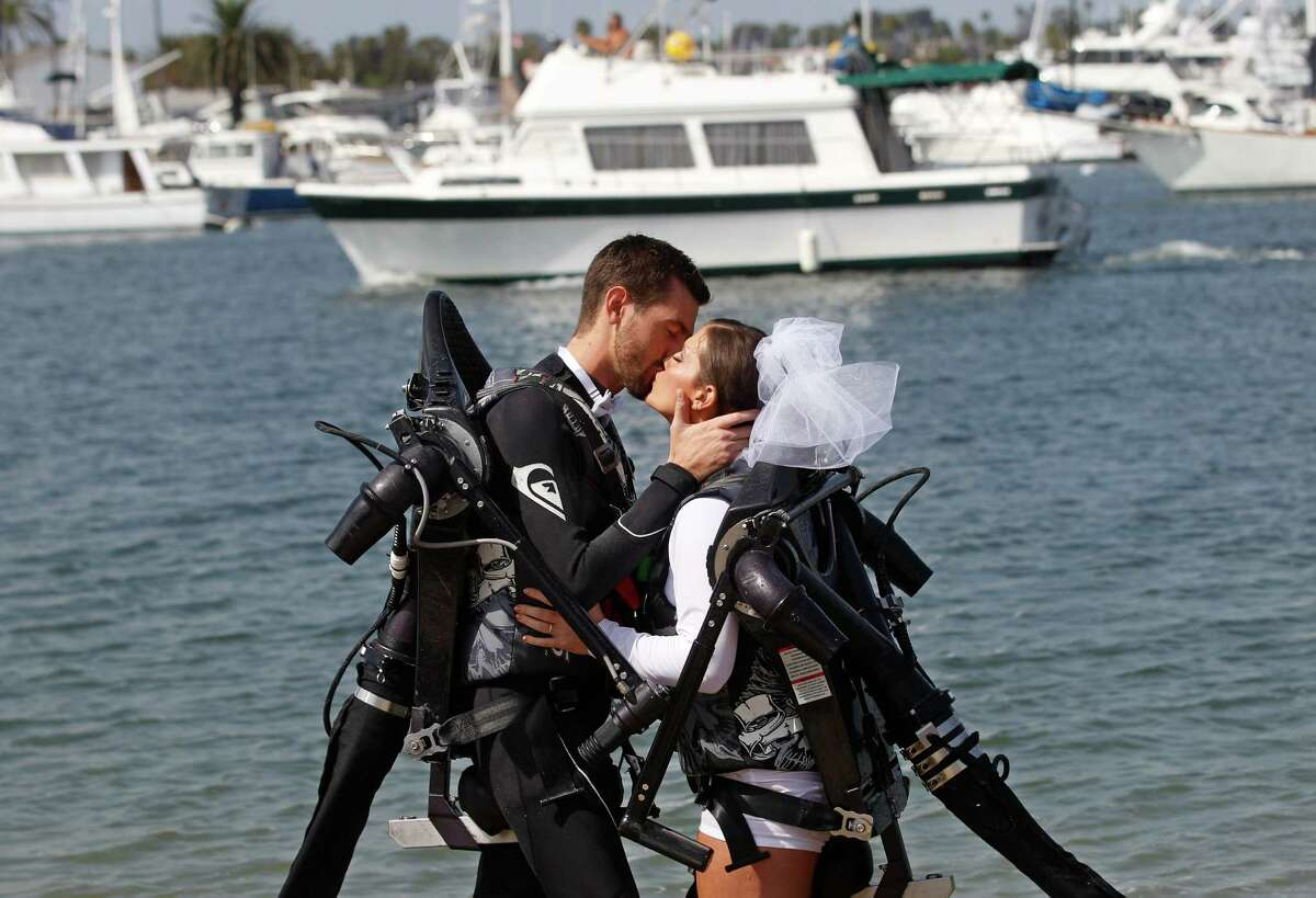 Grant Engler and his new wife, Amanda Engler, wearing jet pack suits, kiss after being pronounced married at their wedding ceremony Thursday, Aug. 23, 2012 in Newport Beach, Calif. The couple arrived at the site by flying in in jet pack suits. The 25-year-old former wedding planner from Grand Rapids, Mich., says she wanted a unique ceremony. So the couple donned the (Canadian) $90,000 (C72,000) contraptions on their backs, along with a wetsuit for the groom and white board shorts and a rash-guard shirt for the bride. The jet packs from Jetlev Southwest helped the couple hover a few feet above the water, to the cheers of their wedding guests. Everything went smoothly, except for a kayaker who capsized during the newlyweds' first dance on the water.