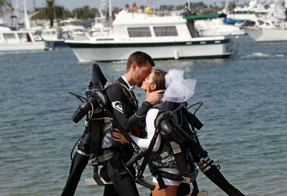 Grant Engler and his new wife, Amanda Engler, wearing jet pack suits, kiss after being pronounced married at their wedding ceremony Thursday, Aug. 23, 2012 in Newport Beach, Calif.  The couple arrived at the site by flying in in jet pack suits. The 25-year-old former wedding planner from Grand Rapids, Mich., says she wanted a unique ceremony. So the couple donned the (Canadian) $90,000 (C72,000) contraptions on their backs, along with a wetsuit for the groom and white board shorts and a rash-guard shirt for the bride. The jet packs from Jetlev Southwest helped the couple hover a few feet above the water, to the cheers of their wedding guests. Everything went smoothly, except for a kayaker who capsized during the newlyweds' first dance on the water. Photo: Lenny Ignelzi, AP / AP