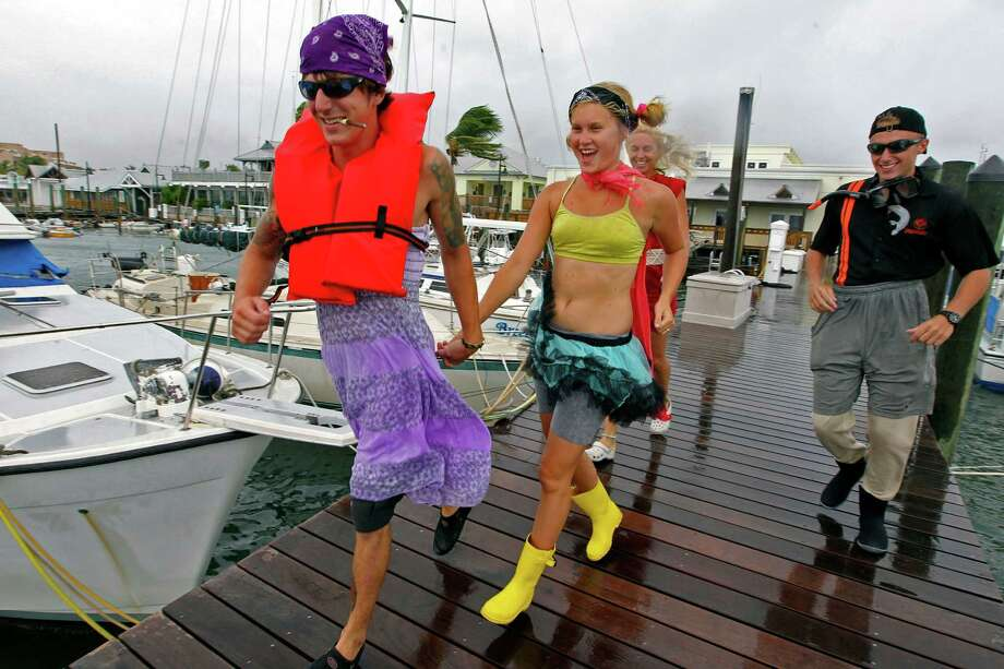 Anton Snitgen, Jenna Curl, Jackie Curl and Michael Manemut run along a dock at Key West Bight Marina in Key West, Fla., as Tropical Storm Isaac hits the area on Sunday, Aug., 26, 2012. Isaac gained fresh muscle Sunday as it bore down on the Florida Keys, with forecasters warning it could grow into a dangerous Category 2 hurricane as it nears the northern Gulf Coast. (AP Photo/The Miami Herald, Walter Michot) Photo: AP, MBO / The Miami Herald