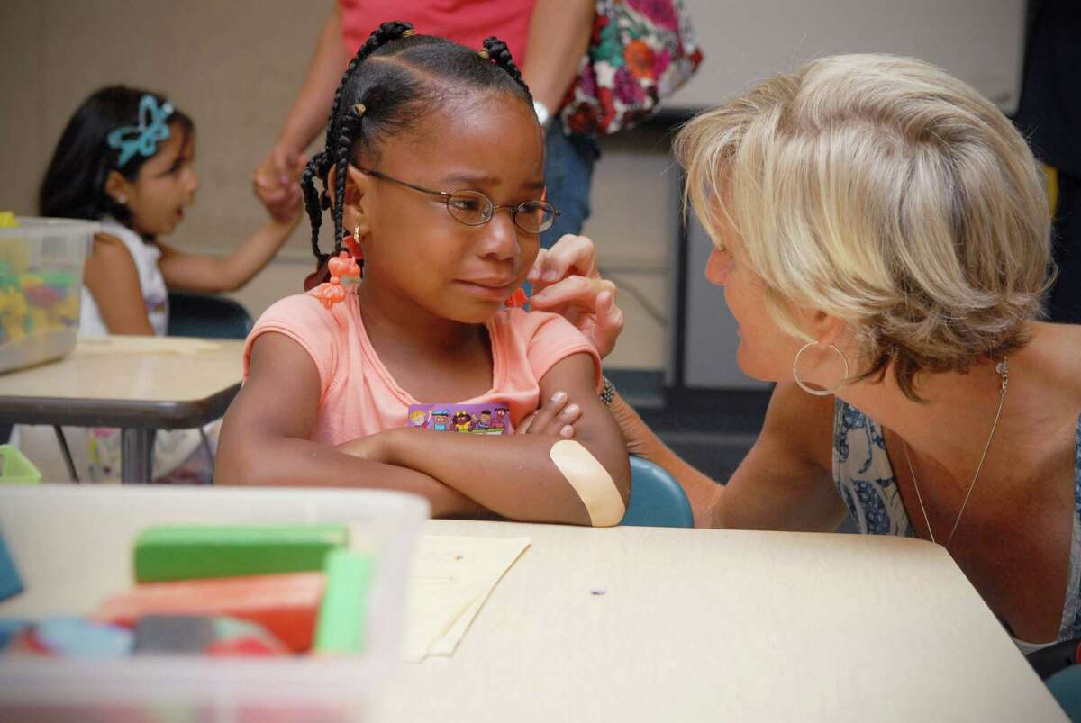 Amber Powell is comforted by Cathy Linn, who's son Michael is also in the class, in Joan Riordian's kindergarten class during orientation day at Newfield Elementary School in Stamford, Conn. on Monday August 27, 2012.