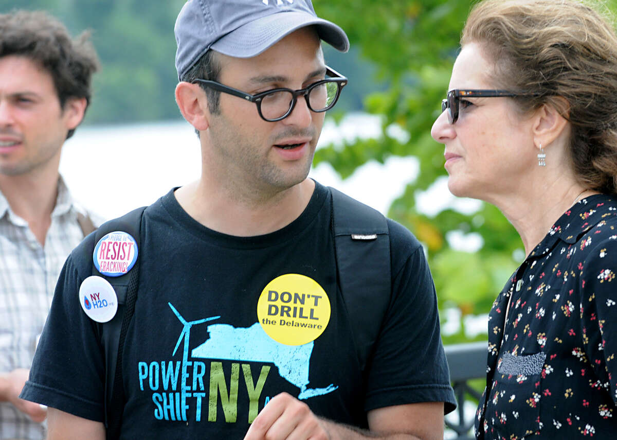 Filmmaker Josh Fox talks to actress Debra Winger while participating in an anti-fracking rally Monday at the Corning Preserve in Albany. (Lori Van Buren / Times Union)