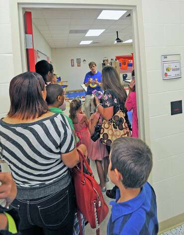 Fifth grade teacher Patricia Velzeboer, center, has a line of students and parents at her door waiting to greet her. Sallie Curtis Elementary School had its grand opening and official dedication Friday August 24, 2012.  BISD officials, school board trustees, students, teachers and staff were all on hand to help cut the ribbon and then tour the last of the new schools to be built with bond money.   Dave Ryan/The Enterprise Photo: Dave Ryan
