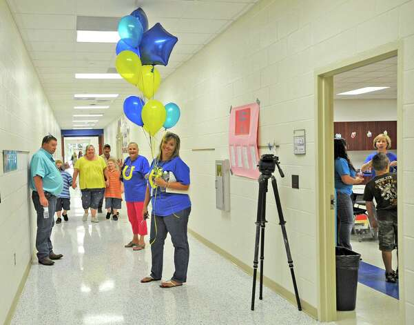 Julie Warner carries balloons through the halls back to the main office. Sallie Curtis Elementary School had its grand opening and official dedication Friday August 24, 2012.  BISD officials, school board trustees, students, teachers and staff were all on hand to help cut the ribbon and then tour the last of the new schools to be built with bond money.   Dave Ryan/The Enterprise Photo: Dave Ryan