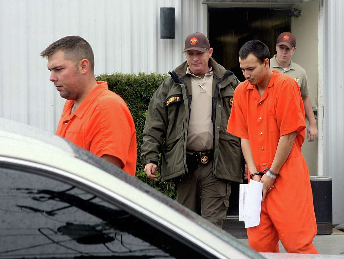 FILE - In this Dec. 12, 2011 file photo, U.S. Army Sgt. Anthony Peden, 25, left, and Pvt. Isaac Aguigui, 19, are led away in handcuffs after appearing before a magistrate judge at the Long County Sheriffs Office in Ludowici, Ga. Prosecutors said Monday, Aug. 27, 2012 that a murder case against four soldiers in Georgia has revealed they formed an anarchist militia within the U.S. military with plans to overthrow the federal government. Prosecutors in rural Long County, near Fort Stewart, said the militia group spent at least $87,000 buying guns and bomb components and was serious enough to kill two people, former soldier Michael Roark and his 17-year-old girlfriend, Tiffany York, by shooting them in the woods last December in order to keep its plans secret. (AP Photo/Lewis Levine, File)