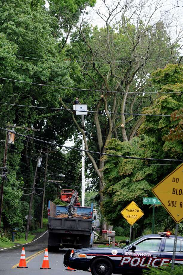 Workers from Hawthorne Brothers Tree Service take down an dangerous tree at  Indian Field Road. Part of Indian Field Road was closes from 10 AM until 4 PM for Emergency Tree Removal the police said. Photo: Helen Neafsey / Greenwich Time
